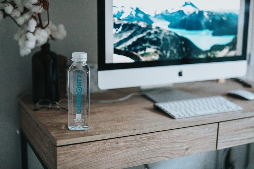 clear plastic bottle beside silver imac