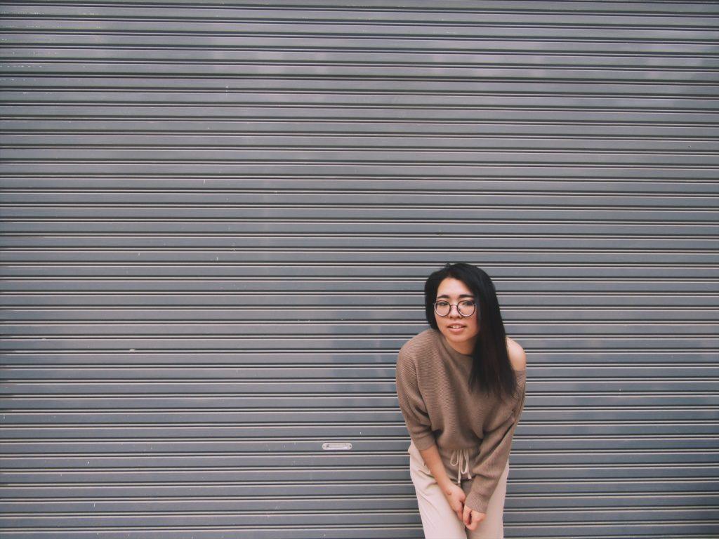 woman leaning on gray garage door